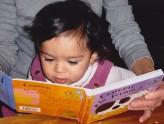 bebe regardant livre dans bras adulte